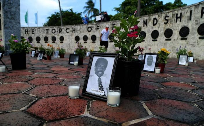 """A small group of protesters honor all victims of police brutality during a protest called """"Say Their Names"""" at the Friendship Torch on Biscayne Boulevard in Miami on Saturday July 4."""