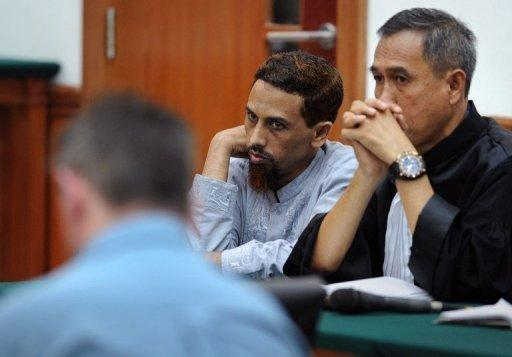 Indonesian Muslim militant and suspected Bali bomber Umar Patek (C) looks on next to his unidentified defense counsel (R) during his trial in Jakarta April 5. Patek, is facing murder charges for the 2002 Bali bombing and five other counts, including bomb-making and illegal firearms possession