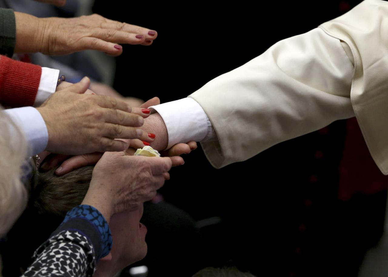 People reach out to touch the hand of Pope Francis as he places it on the head of a person during a special audience with Catholic doctors at the Paul VI hall at the Vatican November 15, 2014. REUTERS/Alessandro Bianchi (VATICAN - Tags: RELIGION)