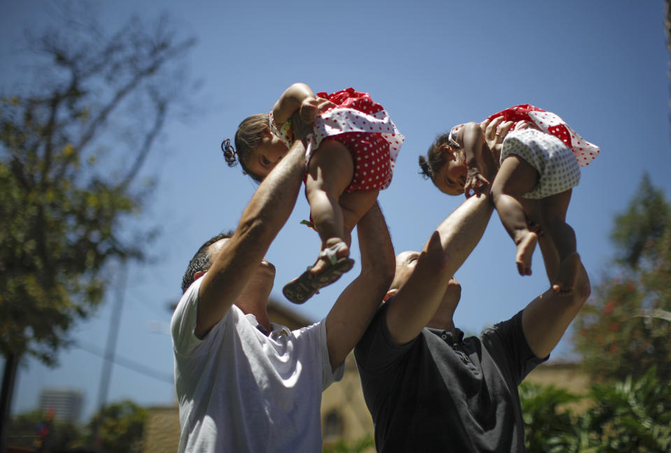 Jason Howe and Adrian Perez hold their one-year-old twin daughters Clara and Olivia at a playground in West Hollywood, California. (Photo: REUTERS/Lucy Nicholson)