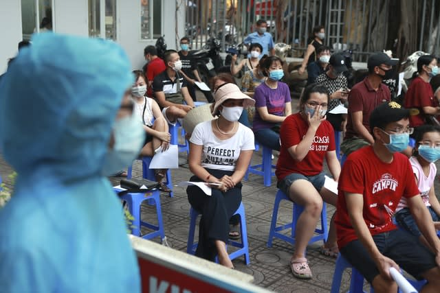 People wait in line for a Covid-19 test in Hanoi, Vietnam (Hau Dinh/AP)