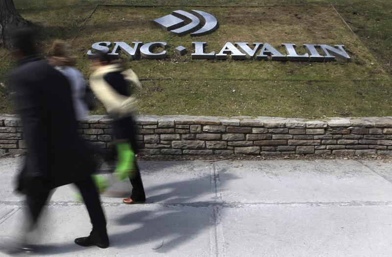 Pedestrians walk past a sign for the head office of SNC Lavalin in downtown Montreal