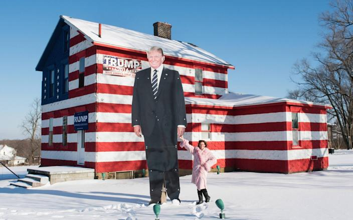 Ms Rossi holds the hand of the 14ft metal cutout of Donald Trump - Joe Appel for the Daily Telegraph