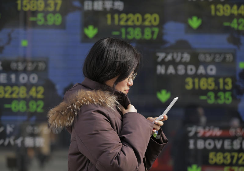 A woman walks by the electronic stock board of a securities firm in Tokyo as Japan's Nikkei 225 dropped 136.87 points to 11,220.20 at one point Friday afternoon, Feb. 8, 2013, slumping after a recent rally spurred by a weakening yen. (AP Photo/Itsuo Inouye)