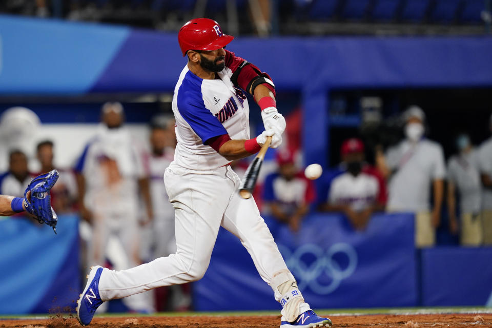 Dominican Republic's Jose Bautista hits the game winning RBI single during the ninth inning of a baseball game against Israel at the 2020 Summer Olympics, Tuesday, Aug. 3, 2021, in Yokohama, Japan. The Dominican Republic won 7-6. (AP Photo/Matt Slocum)