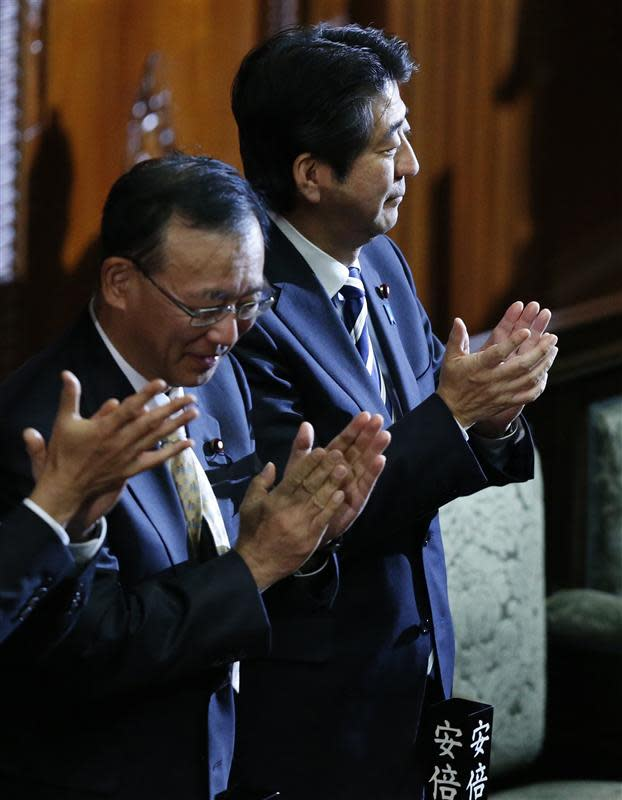 Abe and his cabinet ministers clap as government proposed state secrecy act passed at the Lower House during the plenary session of the parliament in Tokyo