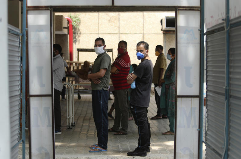 Indians wearing face masks wait to consult doctors at COVID-19 screening facility inside a government run hospital in Jammu, Saturday, June 27, 2020. India is the fourth hardest-hit country by the pandemic in the world after the U.S., Russia and Brazil. (AP Photo/Channi Anand)