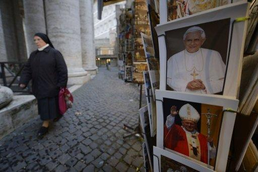 A nun passes by posters showing Pope Benedict XVI and Pope John Paul II at a Vatican shop after it was announced that Pope Benedict XVI will resign on February 11, 2013