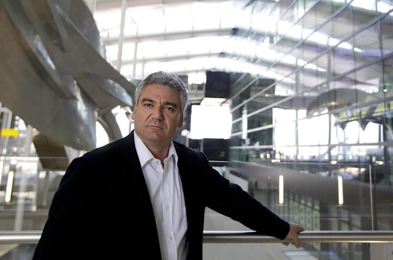 Luis Vidal, Concept and Lead Architect poses for a photograph at the new Heathrow Terminal 2 in London, Wednesday, April 23, 2014, next to the sculpture 'Slipstream', left, by artist Richard Wilson which will be the longest permanent sculpture in Britain, measuring 78 metres and weighing 77 tonnes. The 2.5 billion pound ($4.2 billion) new Terminal 2 is due to open to the public in June after 5-years in development, to handle the anticipated 20 million passengers per year. (AP Photo/Kirsty Wigglesworth)