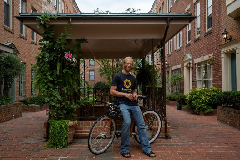 Tarek Maassarani, who adopts a low consumption and carbon footprint lifestyle, poses for a photo with his bicycle with a frame that is over a decade old, at his friend's apartment complex's garage in Washington (AFP Photo/Alastair Pike)