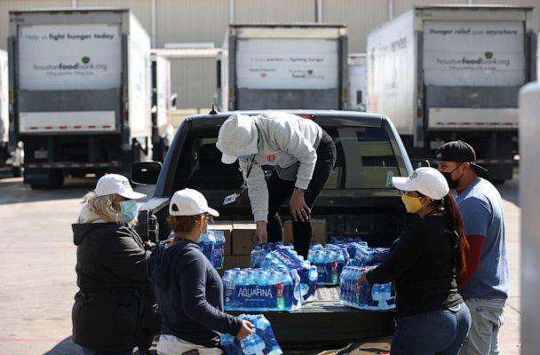 PHOTO: Volunteers load cases of water and emergency food boxes into a truck at the Houston Food Bank on Feb. 20, 2021 in Houston, Texas. (Justin Sullivan/Getty Images)