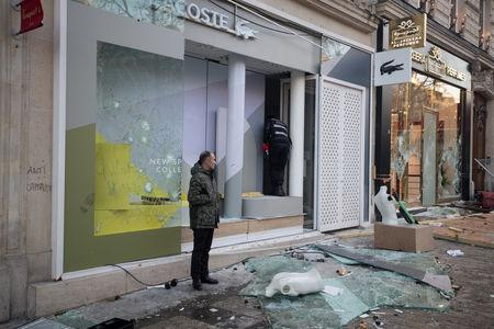 "A man stand in front of a damaged shop on the Champs Elysees avenue during a demonstration by the ""yellow vests"" movement in Paris"