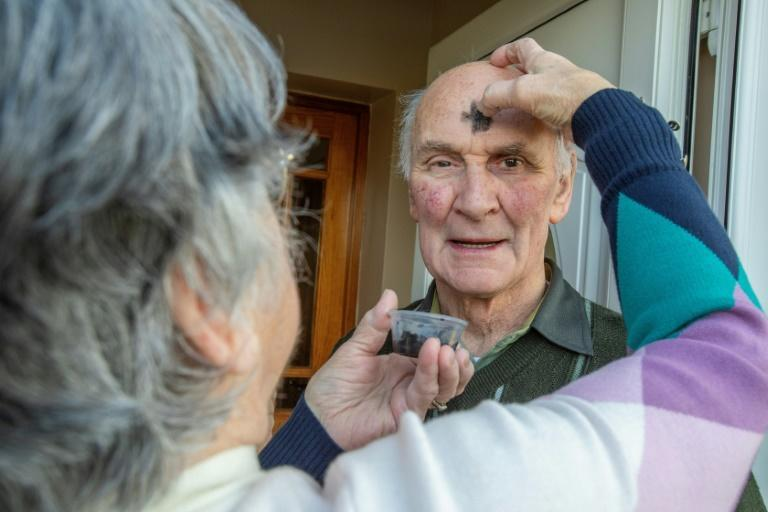 Sally McDonald annoints husband Mac with a cross on the forehead with blessed takeaway ashes for Ash Wednesday outside their home in Clonmany, County Donegal.