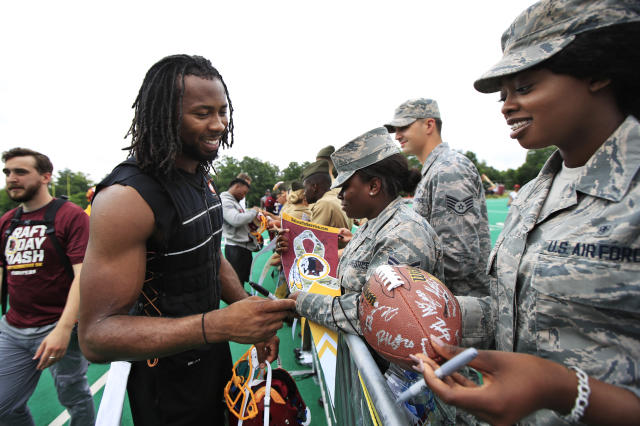 Redskins cornerback Josh Norman (L) signs autographs for military members following a practice. (AP)