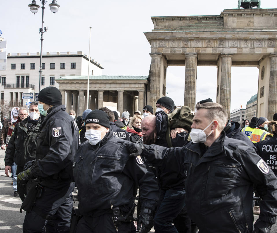 A participant in a demonstration of right-wing extremists and so-called Reich citizens is arrested by police at the Brandenburg Gate in Berlin, Germany, Saturday, March 20, 2021. (Paul Zinken/dpa via AP)