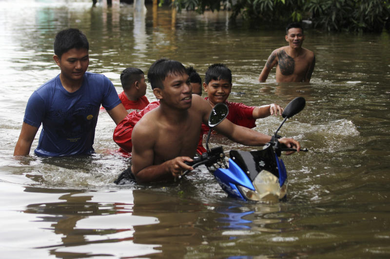 Residents push a motorbike at a flooded neighborhood in Makassar, South Sulawesi, Indonesia, Wednesday, Jan. 23, 2019. Torrential rains that overwhelmed a dam and caused landslides killed at least six people and displaced more than 2,000 in central Indonesia, officials said Wednesday. (AP Photo/Masyudi Syachban Firmansyah)