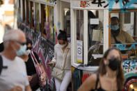 Passengers wearing face masks get off the Gloria funicular in Lisbon, Saturday, Oct. 9, 2021. Portuguese authorities announced Saturday that the country has reached its target of 85 percent of the population fully inoculated against COVID-19. (AP Photo/Armando Franca)