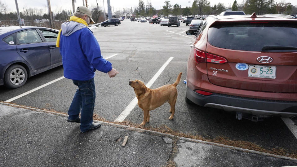 State Rep. Glen Aldrich, R-Gilford, N.H., stretches his legs and plays with his dog Liberty while taking a break from sitting in his car during an outdoor meeting of the New Hampshire House of Representatives in a parking lot, due to the COVID-19 virus outbreak, at the University of New Hampshire Wednesday, Jan. 6, 2021, in Durham, N.H. Aldrich parked in the last row of the large parking lot gathering, which hosted the 400 member N.H. House. (AP Photo/Charles Krupa)