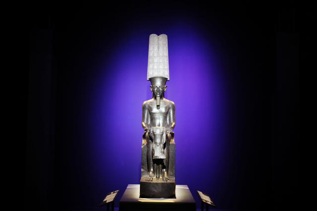 """A statue of """"The god Amun protecting Tutankhamun"""" is displayed as part of 'Tutankhamun, the treasure of the Pharaoh', an exhibition in partnership with the Grand Egyptian Museum at the Grande Halle of La Villette in Paris, France, Thursday, March 21, 2019. (AP Photo/Francois Mori)"""