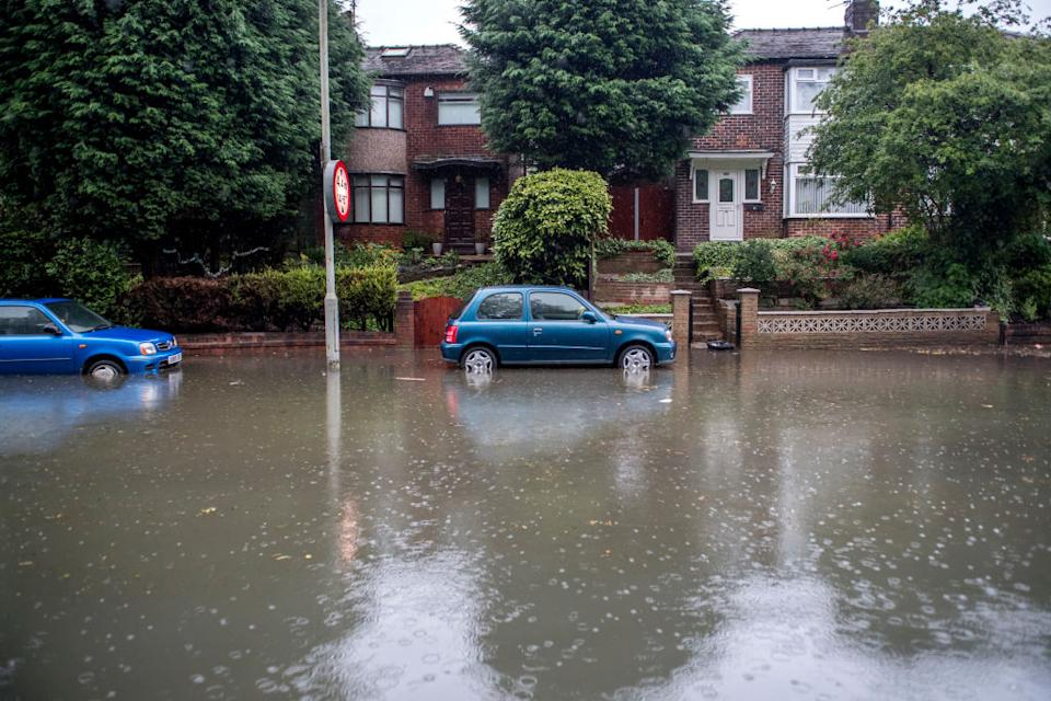 Cars are seen trapped in flood water on Crossley Road near Levenshulme following heavy rainfall (Picture: Getty)