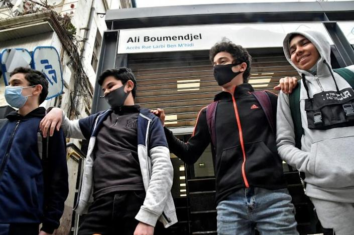 Algerian teens beneath a street name plaque honouring Ali Boumendjel, an Algerian lawyer and independence figure killed by the French during