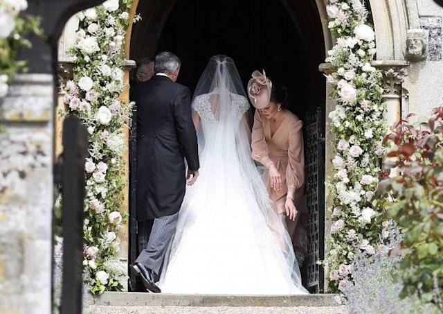 The Duchess of Cambridge adjusts PIppa's train and veil as the bride walks into St Mark's church. (Photo: PA)