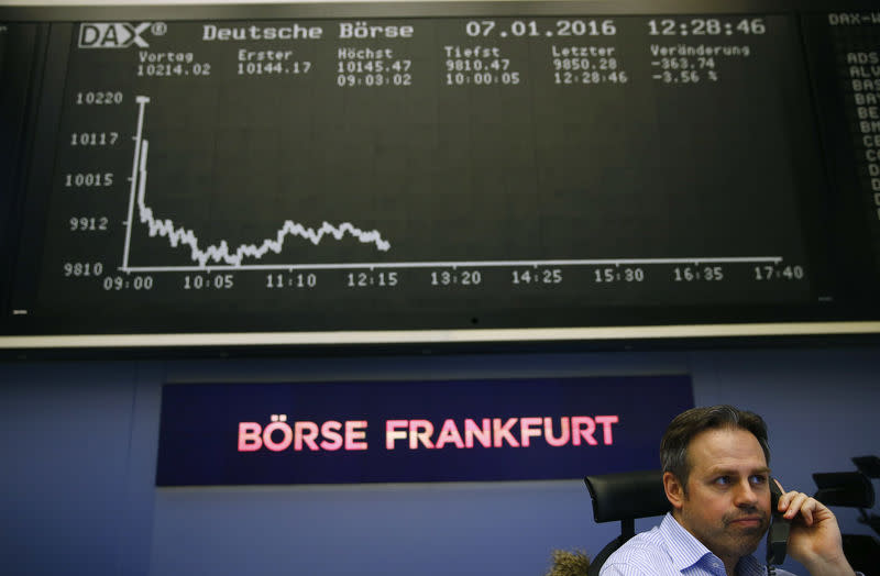 Trader speaks on phone in front of DAX board at Frankfurt's stock exchange