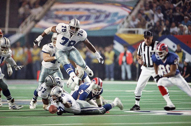 File-This Jan. 30, 1994, file photo shows Dallas Cowboys' Leon Lett (78) jumping over players pursing a fumble by Buffalo Bills' Thurman Thomas during the first quarter of the Super Bowl at the Georgia Dome in Atlanta. Lett, a soft-spoken defensive lineman, had not commented to reporters since a Thanksgiving Day blunder led to a Dallas Cowboys loss. He couldn't escape media day in Atlanta and it was downright painful to watch. (AP Photo/John Gaps III, File)