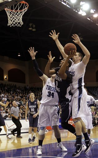 Brigham Young's Brandon Davies, second from right, shoots between Chris Manresa (34) and Dennis Kramer, right, in the first half during an NCAA college basketball game Monday, Jan. 16, 2012, in San Diego. (AP Photo/Gregory Bull)