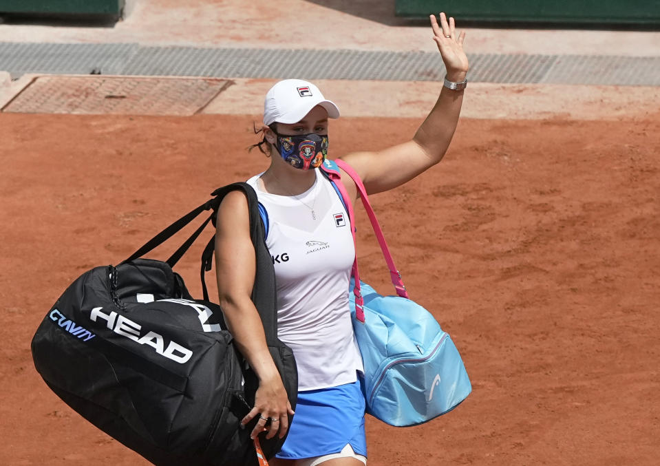 Australia's Ashleigh Barty waves goodbye as she retires with an injury as she was playing against Poland's Magda Linette during their second round match on day 5, of the French Open tennis tournament at Roland Garros in Paris, France, Thursday, June 3, 2021. (AP Photo/Michel Euler)