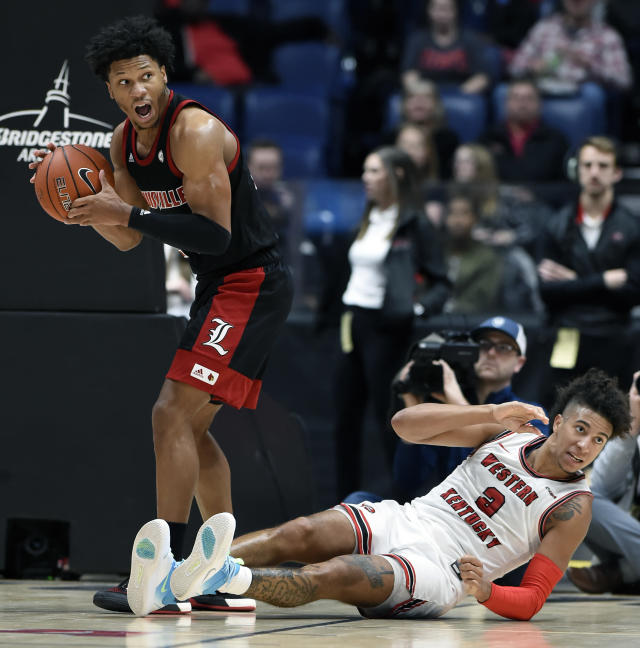 Louisville forward Dwayne Sutton, left, looks at the official after being called for a foul during a scramble for the ball with Western Kentucky guard Jared Savage (2) in the second half of an NCAA college basketball game Friday, Nov. 29, 2019, in Nashville, Tenn. (AP Photo/Mark Zaleski)