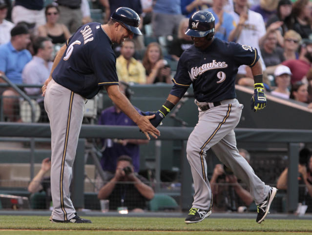 Milwaukee Brewers third base coach Ed Sedar (6) congratulates Jean Segura (9) who runs home after hitting his second home run of against the Colorado Rockies Brewers in the third inning of a baseball game in Denver, Friday, June 20, 2014.(AP Photo/Joe Mahoney)