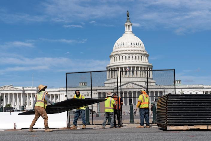 July 10, 2021: Workers remove the fence surrounding the U.S. Capitol building, six months after it was erected following the Jan. 6 riot at the Capitol in Washington.