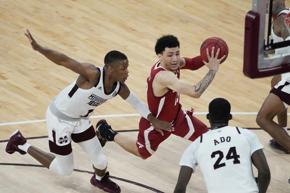 Alabama guard Jahvon Quinerly (13) dribbles past Mississippi State guard Iverson Molinar (1) during the second half of an NCAA college basketball game in Starkville, Miss., Saturday, Feb. 27, 2021. (AP Photo/Rogelio V. Solis)