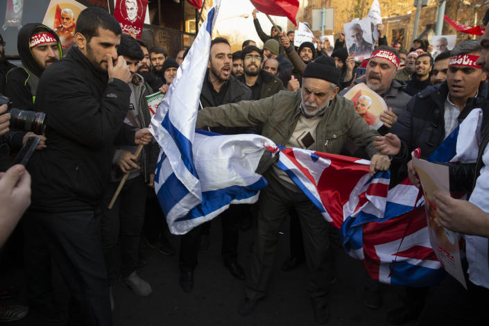 TEHRAN, IRAN - JANUARY 12: Protesters chant slogans and hold up posters of Gen. Qassem Soleimani while preparing to burn representations of British and Israeli flags, during a demonstration in front of the British Embassy on January 12, 2020 in Tehran, Iran. A candlelight vigil held late on Saturday in Tehran, to remember the victims of the Ukrainian plane crash, turned into a protest with hundreds of people chanting against the country's leaders including Supreme Leader Ayatollah Ali Khamenei and police dispersing them with tear gas. Police briefly detained the British ambassador to Iran, Rob Macaire, who said he went to the Saturday vigil without knowing it would turn into a protest.  (Photo by Majid Saeedi/Getty Images)