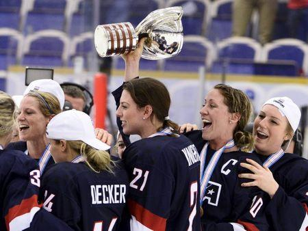 Team USA players including Hilary Knight (#21), Meghan Duggan (#10) and Brianna Decker (R) celebrate with the World Cup trophy after the 2015 IIHF Ice Hockey Women's World Championship gold medal match between USA and Canada at Malmo Isstadion in Malmo, southern Sweden, on April 4, 2015. REUTERS/Claudio Bresciani/TT News Agency