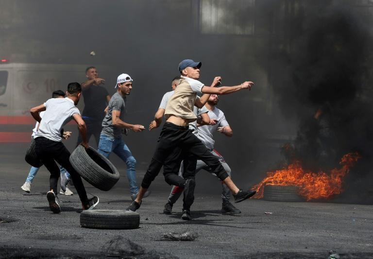 Palestinian protesters hurl rocks amid confrontations with Israeli security forces at the Hawara checkpoint south of Nablus city in the occupied West Bank on May 21