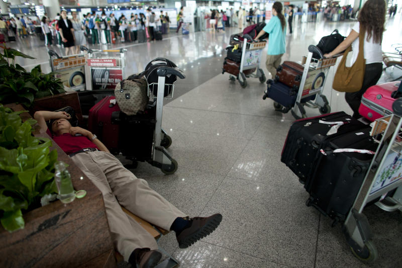 In this Thursday Aug. 1, 2013 photo, a passenger sleeps on a bench while waiting for his flight at Terminal 3 of Beijing International Airport in Beijing, China. China's fast growing air travel market is the world's second biggest. But when it comes to flight delays, it's No. 1. According to official figures, 75 percent of China's flights left on time last year. But private surveys paint a different picture. A recent report by travel industry monitor FlighStat Inc. found that just 18 percent of flights at Beijing's airport left on time in June, the lowest proportion among 35 airports worldwide, with Shanghai second at 29 percent. Eight of the 10 worst performing airlines were mainland Chinese carriers. (AP Photo/Alexander F. Yuan)