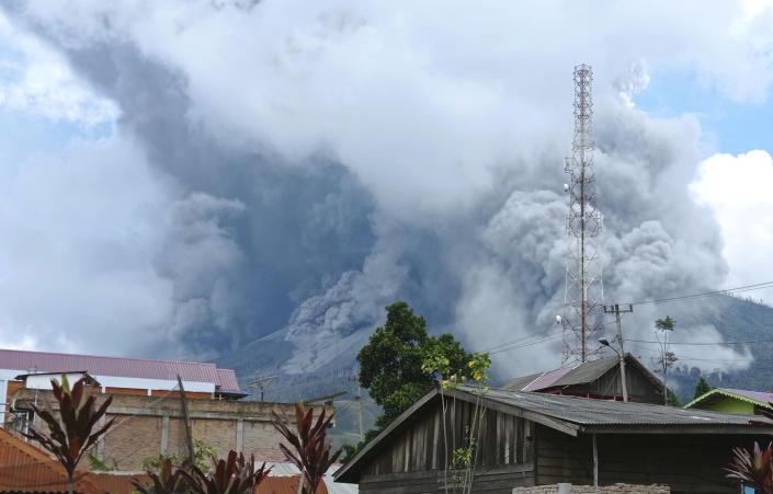 Mount Sinabung releases volcanic materials during an eruption as seen from a school yard in Karo, North Sumatra, Indonesia, Wednesday, July 28, 2021. The rumbling volcano on Indonesia's Sumatra island on Wednesday shot billowing columns of ash and hot clouds down its slopes. (AP Photo/Sastrawan Ginting)