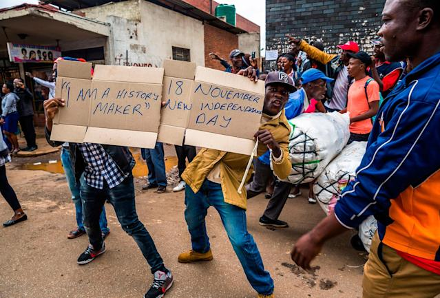<p>People carry makeshift signs during a demonstration demanding the resignation of Zimbabwe's president on Nov. 18, 2017 in Harare. (Photo: Jekesai Njikizana/AFP/Getty Images) </p>