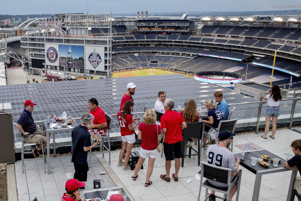 People watch the game from the Top of the Yard bar on the rooftop of Hampton Inn & Suites hotel during an opening day baseball game between the New York Yankees and the Washington Nationals at Nationals Park, Thursday, July 23, 2020, in Washington. (AP Photo/Andrew Harnik)