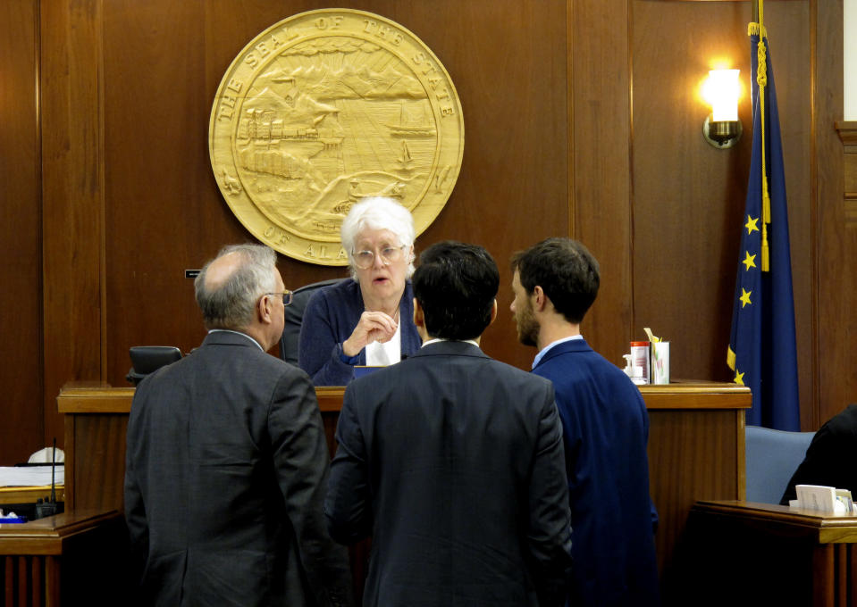 Alaska House Speaker Louise Stutes, second from left, speaks to colleagues during a break in the House floor session on the opening day of the second special session on Wednesday, June 23, 2021, in Juneau, Alaska. Pictured are, from left, Reps. Bryce Edgmon, Stutes, Neal Foster and Zack Fields. (AP Photo/Becky Bohrer)