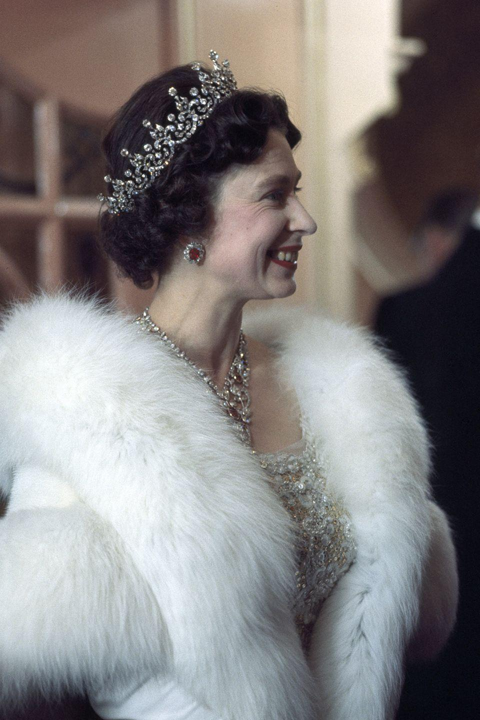 <p>In a white lace dress, fur coat, and a mix of diamond and ruby jewels. </p>
