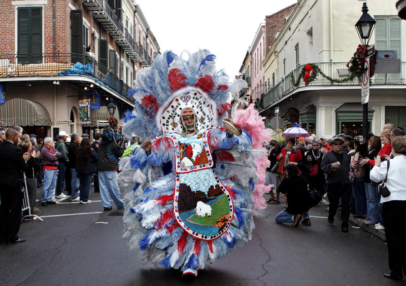 "FIE - In this Jan. 1, 2008 file photo, ""Big Chief"" Alfred Doucette, dances in a parade on Royal Street in the French Quarter of New Orleans. When the Mardi Gras Indians take to the street the elaborate beads and waving feathers will stop traffic and start the cameras clicking. Now they hope that when those taking pictures of them and their suits resell them, they will be in line for some of that profit. Ashlye Keaton, an adjunct law professor at Tulane, has been working with the Mardi Gras Indians to help them copyright their costumes.  (AP Photo/Judi Bottoni, File)"