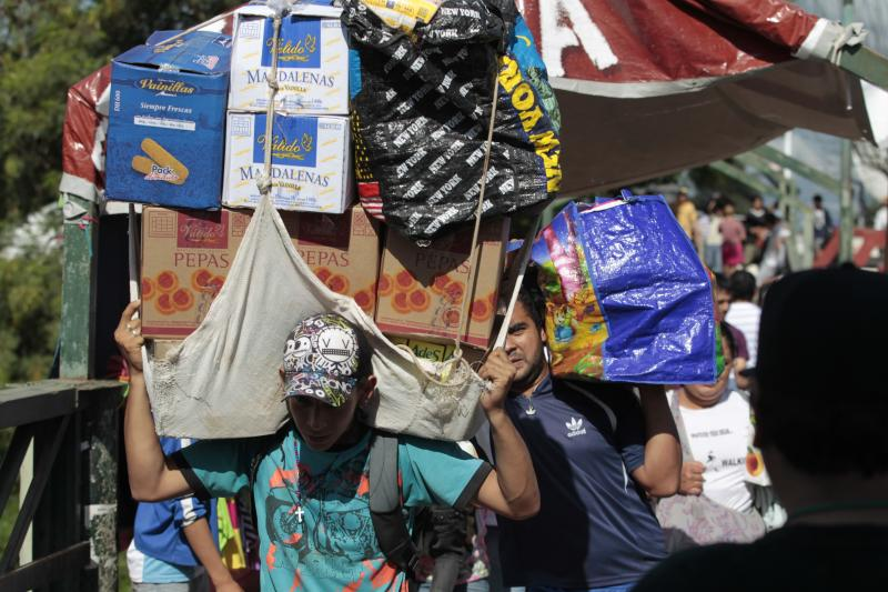 In this June 1, 2013 photo, Paraguayans returning from shopping in Clorinda, Argentina carry boxes and bags across the international bridge over the Pilcomayo River into the town of Nanawa, Paraguay. Shoppers who turn to the street rather than the banks to swap their dollars are getting a bonanza of extra Argentine pesos and can shop much more cheaply than back at home due to Argentina's currency controls and black market for US dollars. Taking advantage of the guarani's newfound strength, Paraguayans are rolling by the thousands into the Argentine frontier city of Clorinda to do their shopping. (AP Photo/Jorge Saenz)