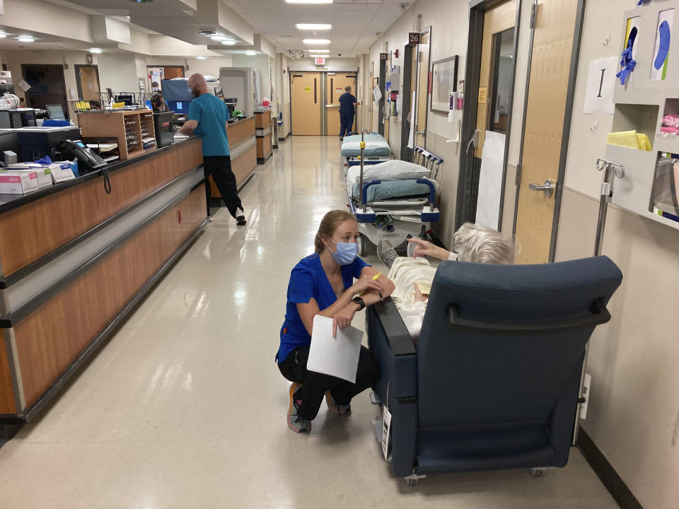 FILE - In this Aug. 20, 2021, file photo, a nurse talks to a patient in the emergency room at Salem Hospital in Salem, Ore., with gurneys lining the hallway behind them, ready to take patients if needed. Gov. Kate Brown announced Wednesday, Aug. 25, 2021, that the state has contracted with a medical staffing company to provide up to 500 health care workers to hospitals around the state to help respond to the surge in patients due to the delta variant. (AP Photo/Andrew Selsky, File)