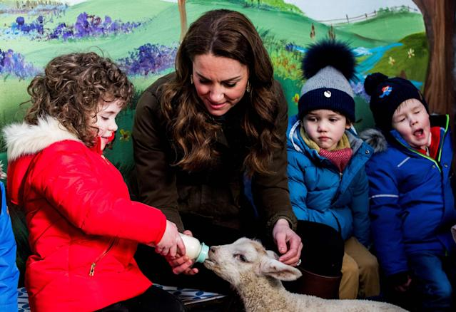 Kate helps feed a lamb at the farm. (Getty Images)