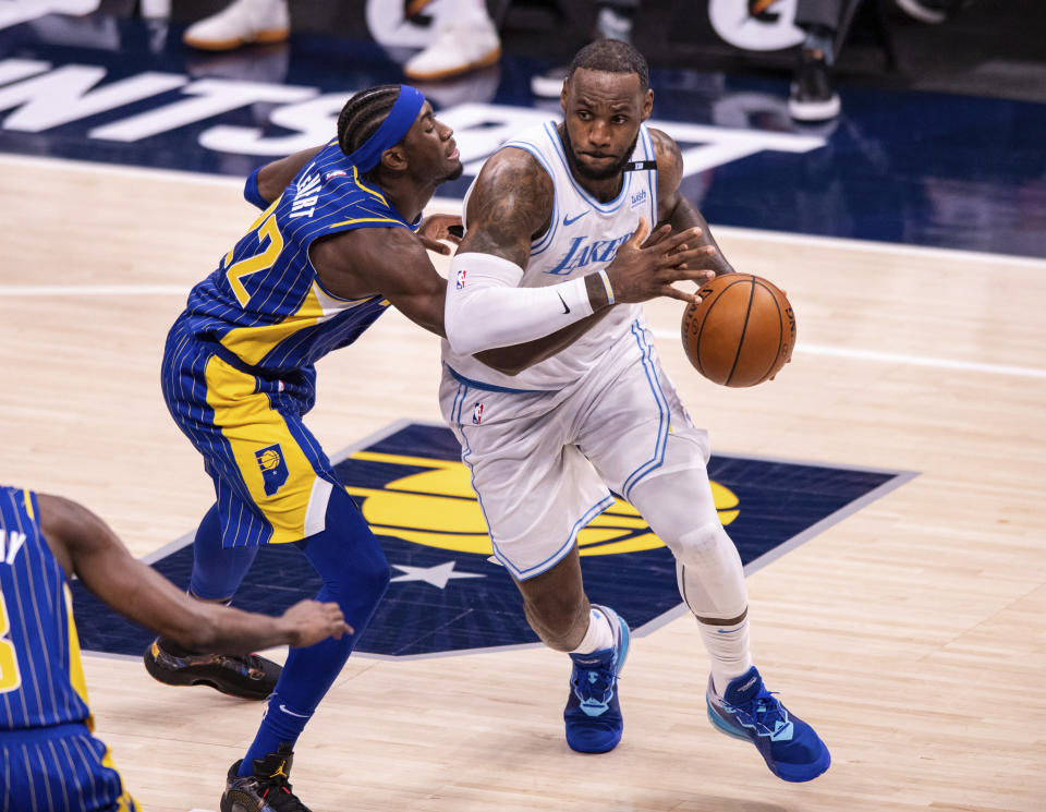 Indiana Pacers guard Caris LeVert (22) knocks the ball out of the hands of Los Angeles Lakers forward LeBron James (23) as he makes a move along the baseline during the first half of an NBA basketball game in Indianapolis, Saturday, May 15, 2021. (AP Photo/Doug McSchooler)