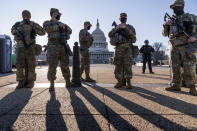 """Members of the Michigan National Guard and the U.S. Capitol Police keep watch as heightened security remains in effect around the Capitol grounds since the Jan. 6 attacks by a mob of supporters of then-President Donald Trump, in Washington, Wednesday, March 3, 2021. The U.S. Capitol Police say they have intelligence showing there is a """"possible plot"""" by a militia group to breach the Capitol on Thursday. (AP Photo/J. Scott Applewhite)"""