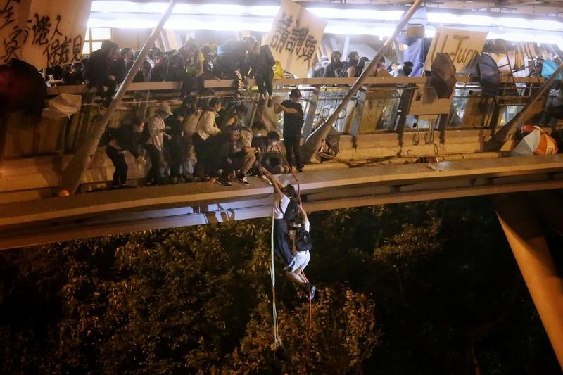 Anti-goverment protesters trapped inside Hong Kong Polytechnic University abseil onto a highway and escape before being forced to surrender during a police besiege of the campus in Hong Kong